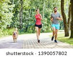 happy couple running with dog... | Shutterstock . vector #1390057802