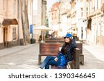 a young woman sits on a bench... | Shutterstock . vector #1390346645