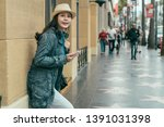 hipster asian girl dressed in urban style leans against wall with smartphone in hands. teenager female traveler searching direction online map on cellphone standind on hollywood walk of fame stret.