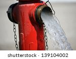 Small photo of powerful water flow coming out with impetus from a street hydrant Red