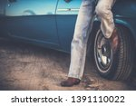 Western Country Driver. Cowboy Shoes and Classic Jeans Wearing. Men in Front of His Classic Muscle Car. Closeup Road Trip Concept. - stock photo