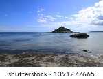 Looking across the water towards St Michaels Mount in Cornwall. The tide is in and the causway is covered with water.