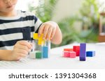 Stock photo closeup of a little boy s hands playing colorful block puzzles problem solving cognitive skill 1391304368