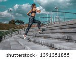 Stock photo girl runs in the summer in the city on the morning run stair background blue sky with clouds 1391351855