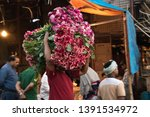 Small photo of New Dehi, India - March 2018; Merchants at Phool Mandi in Ghazipur prepare and sell flowers for the ancient Hindu festival of colors, Holi, celebrating the victory of the superior over the immoral.