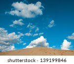 top of a sand dune with blue sky and clouds and copy space - stock photo