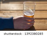 close up as man holds pint of... | Shutterstock . vector #1392380285
