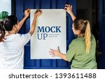 women putting up a poster mockup | Shutterstock . vector #1393611488
