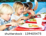 Stock photo elementary pupils enjoying healthy lunch in cafeteria 139405475