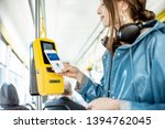 Stock photo woman paying conctactless with smartphone for the public transport in the tram 1394762045