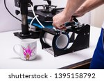 Small photo of Man printing on coffee mugs in workshop