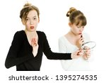 Small photo of Two teenaged girls haggle to get a mirror to make a make up - sister rivalry - white background
