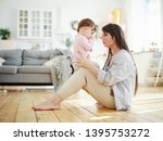 Small photo of Side view of young mother sitting on floor at home and talking to her baby daughter sucking her thumb. Mom trying to break thumb-sucking habit