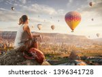 Small photo of woman traveler with red backpack watching the hot air balloons at the hill of Goreme, Cappadocia, Turkey. Cappadocia one of the best places to fly with hot air balloons.