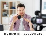 Small photo of blogging, videoblog and people concept - unsure male blogger with camera recording video review of smart speaker and making so-so gesture at home office