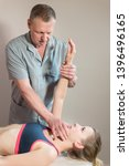 Small photo of Male manual visceral therapist masseur treats a young female patient. Diagnosis of the jaw joint