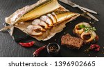 Stock photo appetizing smoked mackerel fish with spices pepper and bread on craft paper over dark stone 1396902665