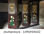 Small photo of Hong Kong, China - March 8, 2019: Tai Fu Tai Ancestral home in New Territory. Frontal Closeup of brown doors with green and gold decorations, movable to close off and separate room.