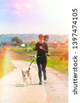 Stock photo girl running with dog outdoors in nature on a rural road sunny day in countryside with beagle dog 1397474105