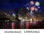 Firework over city at night with reflection in water - stock photo