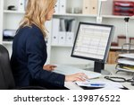 Stock photo side view portrait of businesswoman using computer at office desk 139876522