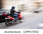 motorcycle rider in the city traffic in motion blur - stock photo