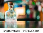 Small photo of Austin, Texas/ USA- May 17, 2019: Silver patron Tequila bottle/container with pink mixed drink on the bottom with colorful warm background in bokeh