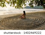 Small photo of the girl sits back on the sandy beach in the center of an impromptu circle and meditates