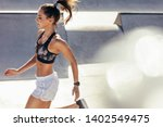 fit woman running outdoors.... | Shutterstock . vector #1402549475