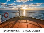 Wooden deck and railing from cruise ship. Beautiful sunset and ocean view. - stock photo