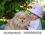 The Girl Hugging A Pomeranian...