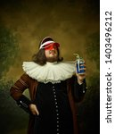 Small photo of Young man as a medieval knight in red cap on dark studio background. Portrait of male model in retro costume. Holding a drink. Human emotions, comparison of eras and facial expressions concept.