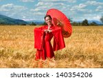 Woman in red clothes with chinese umbrella posing in the wheat field - stock photo