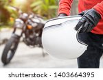 handsome man holding a helmet... | Shutterstock . vector #1403664395