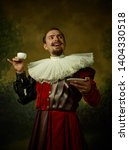 Small photo of Young man as a medieval knight on dark studio background. Portrait in low key of male model in retro costume. Drinking morning coffee. Human emotions, comparison of eras and facial expressions concept