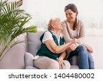 senior lady sitting in armchair ... | Shutterstock . vector #1404480002