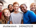 Small photo of Portrait Of Smiling Male And Female Students In Grade School Classroom
