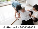 Asian elderly with walking stick on floor after falling down and caring young woman assistant,sick senior or mother fell to the floor because of dizziness and having a daughter,granddaughter to help