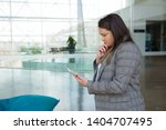 thoughtful business woman using ... | Shutterstock . vector #1404707495