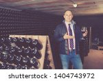 male winemaker giving tour... | Shutterstock . vector #1404743972