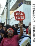 "Small photo of Recife/Pernambuco/Brazil - May 15 2019: Black woman at the education protest holding a protest sign written ""Free Lula"" at the Nacional stoppage against the brazilian government policies"