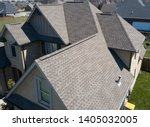 Small photo of Residential shingle roof using ridge vent s with gables visible