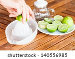 hand squashing fresh lime on... | Shutterstock . vector #140556985