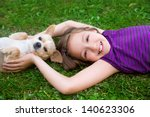 Stock photo children girl playing with chihuahua dog lying on backyard lawn 140623306