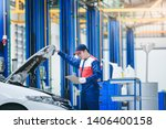 A young Asian car mechanic in a car repair shop is analyzing engine problems and checking the engine. For customers who use the car to repair service., Auto mechanic working in garage - stock photo