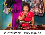 Small photo of local african tailor in her workshop smiling while viewing something on her phone