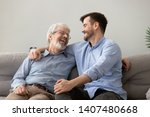 Small photo of Smiling grown son sit on couch relax with senior dad talk sharing thoughts looking in eyes, happy millennial man rest on sofa speak with elderly father enjoy leisure family weekend at home