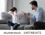 Small photo of Angry young dad sit on couch lecture scold preschooler son closing ears with hands, offended stubborn boy child avoid ignore listening to serious mad father talking, having dispute or quarrel at home