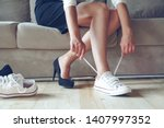 Small photo of Young beautiful woman makes the choice between comfortable and uncomfortable shoes. Beautiful or comfortable shoes concept