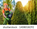 Caucasian Gardener Shaping Tree with Powerful Gasoline Plants Trimmer. Topiary Concept. - stock photo